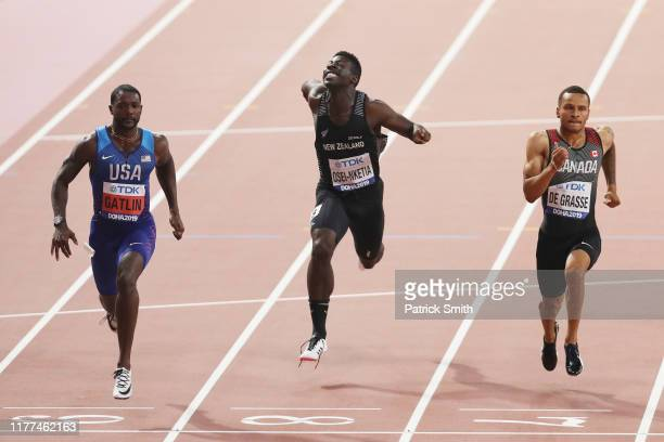 Justin Gatlin of the United States Edward OseiNketia of New Zealand and Andre De Grasse of Canada compete in the Men's 100 Metres heats during day...