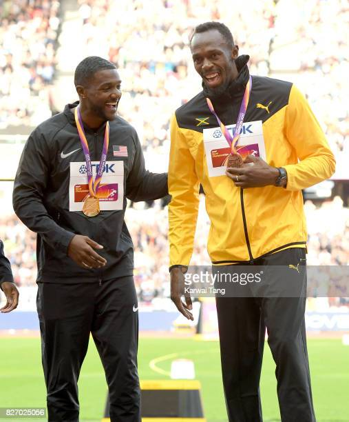 Justin Gatlin of the United States gold and Usain Bolt of Jamaica bronze celebrate during the medal ceremony for the Men's 100 metres during day...