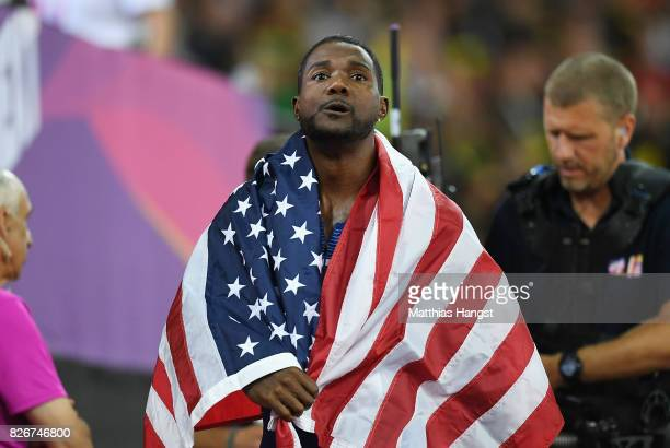 Justin Gatlin of the United States wears his national flag around his shoulders on his lap of honour following his win in the Men's 100 metres final...