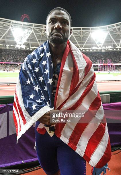 Justin Gatlin of the United States wears his national flag on his shoulders on his lap of honour following his win in the Men's 100 metres Final in...