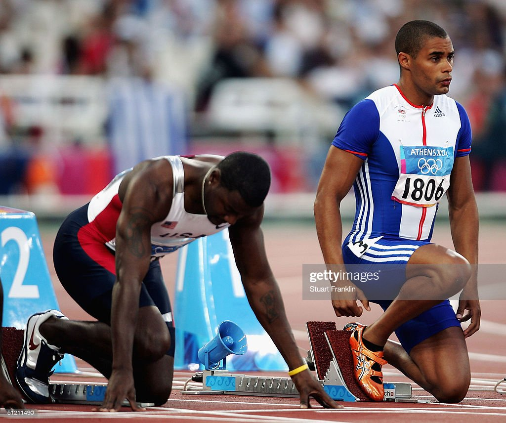 Justin Gatlin of USA and Jason Gardener of Great Britain go down in the blocks for the men's 100 metre event on August 21, 2004 during the Athens 2004 Summer Olympic Games at the Olympic Stadium in the Sports Complex in Athens, Greece.