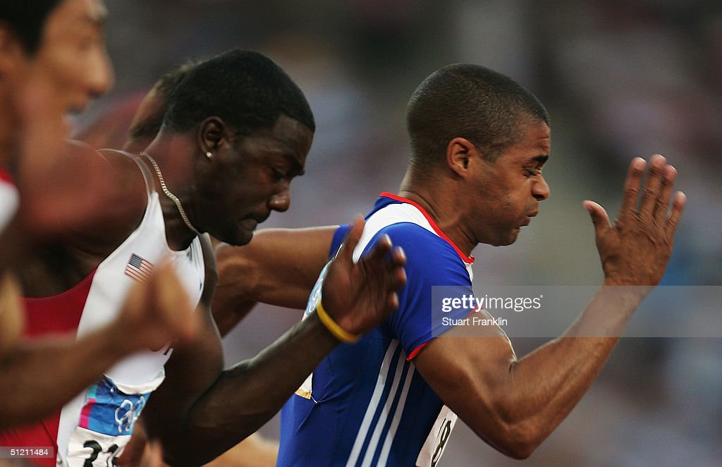 Justin Gatlin of USA and Jason Gardener of Great Britain run in the men's 100 metre event on August 21, 2004 during the Athens 2004 Summer Olympic Games at the Olympic Stadium in the Sports Complex in Athens, Greece.
