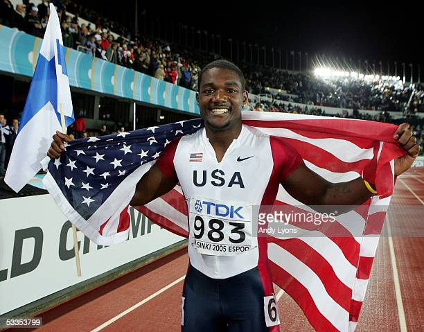 Justin Gatlin of USA holds the an American flag and a finish flag as he celebrates after he won the men's 200 metres final at the 10th IAAF World...