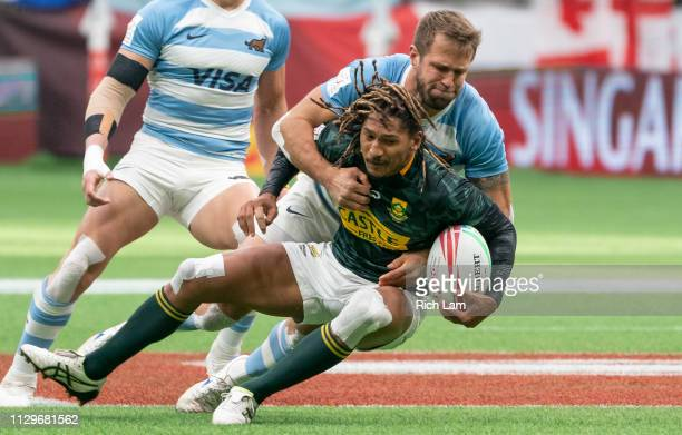 Justin Geduld of South Africa gets tackled by Fernando Luna of Argentina during rugby sevens action on Day 2 of the HSBC Canada Sevens at BC Place on...