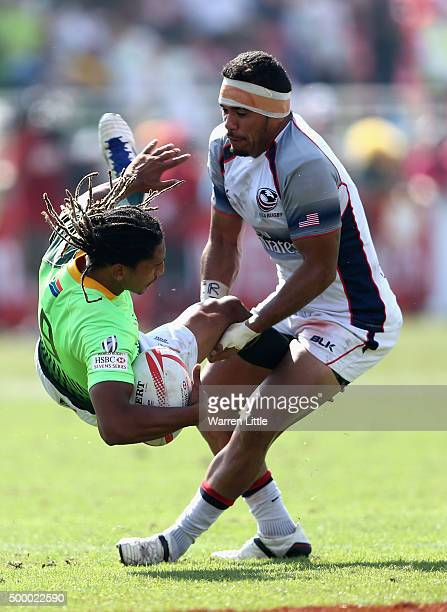 Justin Geduld of South Africa is tackled by Folau Niua of the USA in the Cup quarter final match during the Emirates Dubai Rugby Sevens HSBC World...