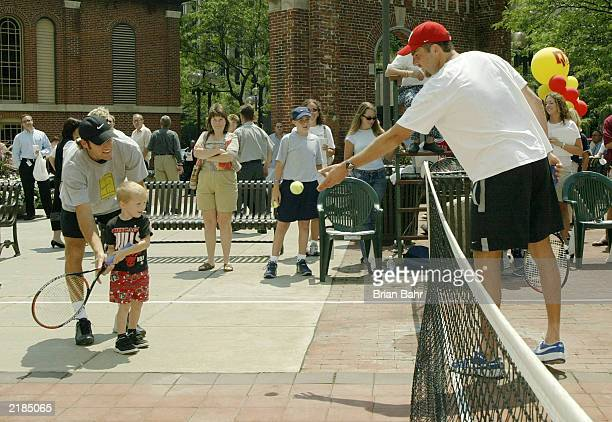 Justin Gimelstob tosses the ball to young Brian Maddox while Robby Ginepri helps as they try to draw attention to the 2003 RCA Championships by...