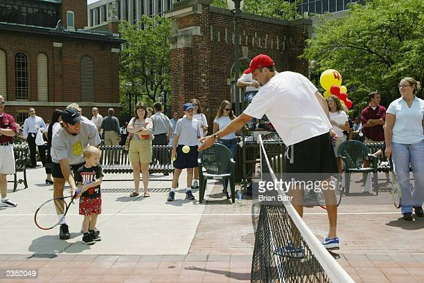 Justin Gimelstob tosses the ball to young Brian Maddox while Robby Ginepri helps as they promote the 2003 RCA Championships by playing a short match...