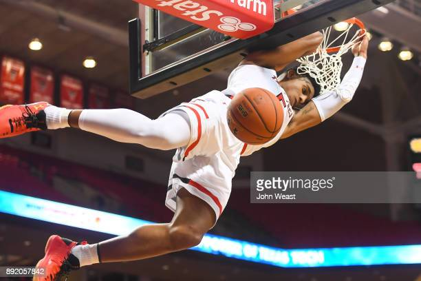 Justin Gray of the Texas Tech Red Raiders hangs on the rim after dunking the basketball during the game against the Kennesaw State Owls on December...