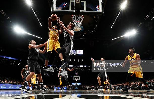 Justin Hamilton of the Brooklyn Nets blocks a shot against Myles Turner of the Indiana Pacers during their game at the Barclays Center on October 28...
