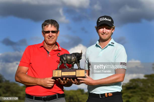 Justin Harding of South Africa and caddy Alan Burns, pose with the trophy during Day Four of the Magical Kenya Open at Karen Country Club on March...