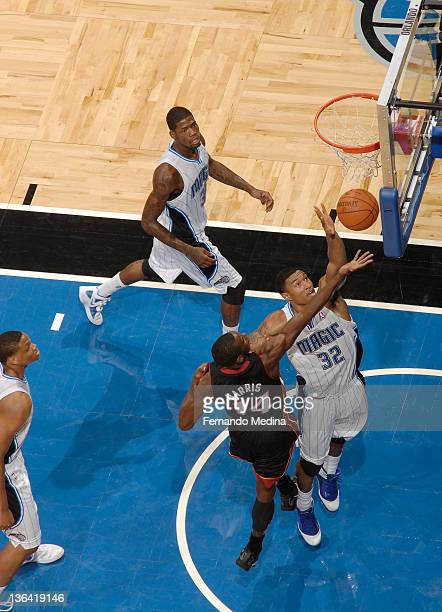 Justin Harper of the Orlando Magic rebounds the basketball against Terrel Harris of the Miami Heat during the preseason game on December 21 2011 at...