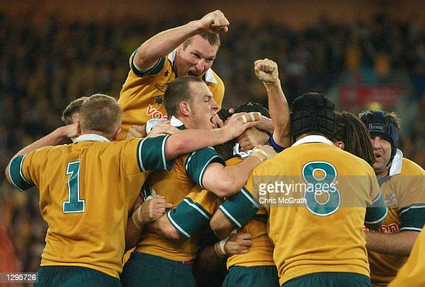 Justin Harrison of the Wallabies celebrates as team mates swamp Matt Burke after he kicked a peanalty goal to win the match during the Tri Nations...