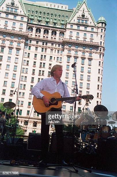 Justin Hayward of The Moody Blues in permformance with the Dakota in the background circa 1990 New York
