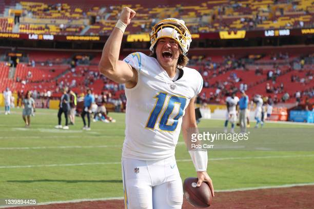 Justin Herbert of the Los Angeles Chargers celebrates after defeating the Washington Football Team 20-16 at FedExField on September 12, 2021 in...
