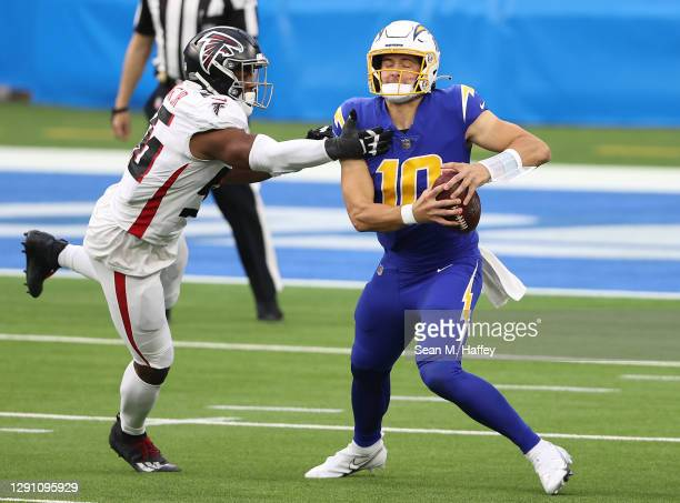 Justin Herbert of the Los Angeles Chargers is pursued by Dante Fowler Jr. #56 of the Atlanta Falcons during the third quarter at SoFi Stadium on...
