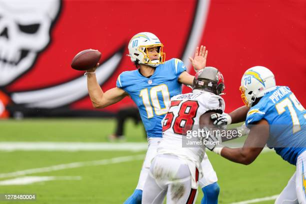 Justin Herbert of the Los Angeles Chargers looks to pass against Shaquil Barrett of the Tampa Bay Buccaneers during the first half of a game at...