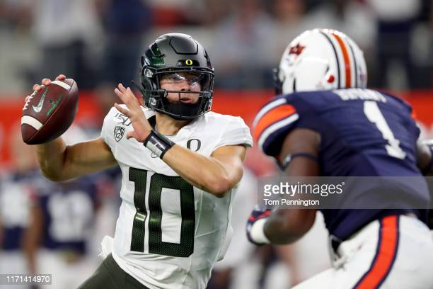 Justin Herbert of the Oregon Ducks looks for an open receiver against the Auburn Tigers in the first quarter during the Advocare Classic at ATT...