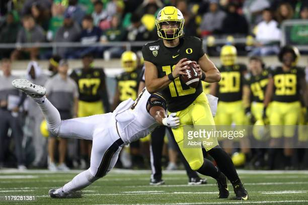 Justin Herbert of the Oregon Ducks looks to throw the ball while being hit by Cameron Goode of the California Golden Bears in the third quarter...