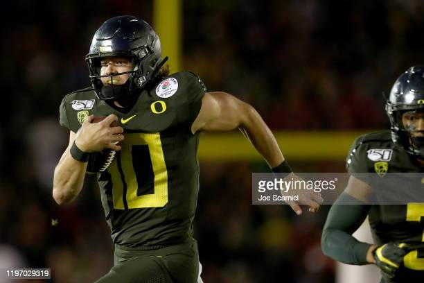 Justin Herbert of the Oregon Ducks runs with the ball to score a 30 yard touchdown against the Wisconsin Badgers during the fourth quarter in the...