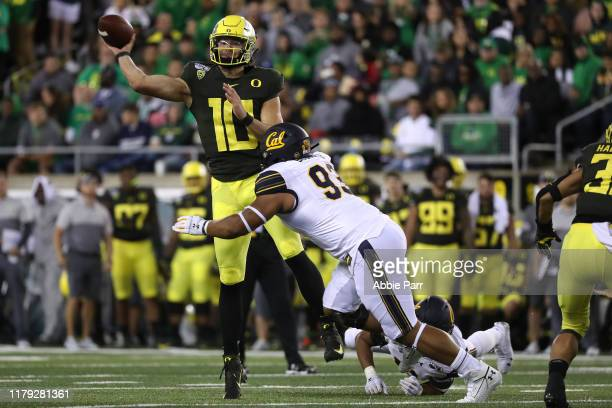 Justin Herbert of the Oregon Ducks throws the ball while being hit by Luc Bequette of the California Golden Bears in the third quarter during their...