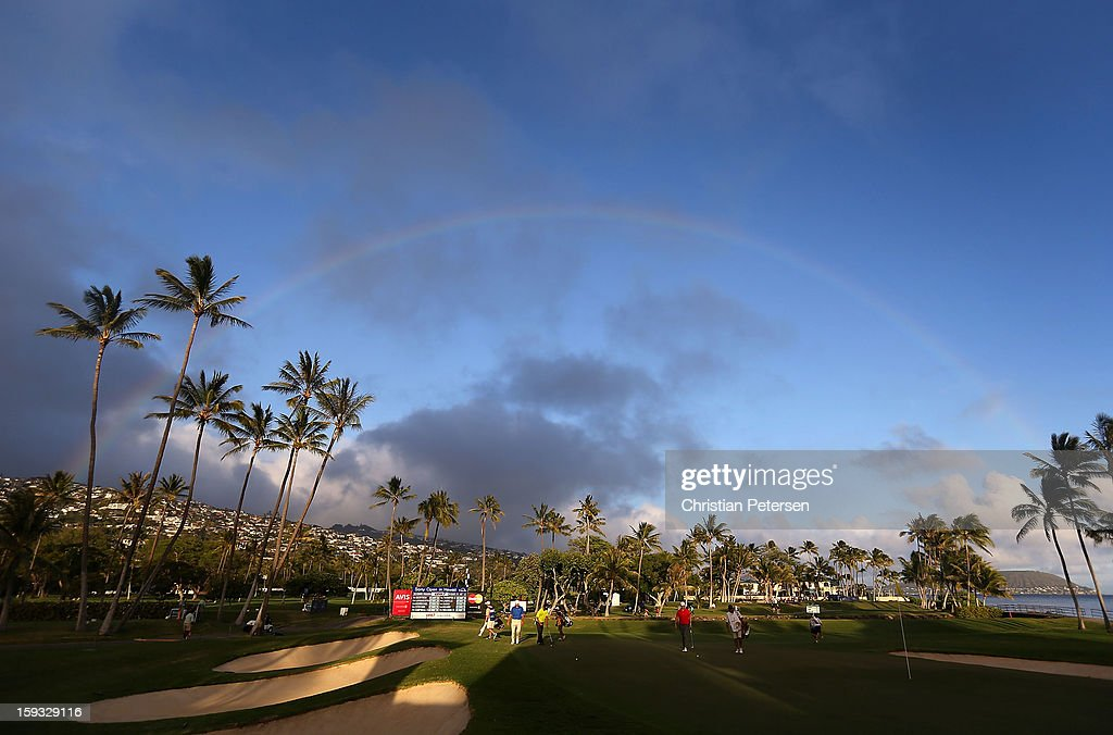 Justin Hicks, Josh Persons and Shawn Stefani approach the 17th green under a rainbow during the second round of the Sony Open in Hawaii at Waialae Country Club on January 11, 2013 in Honolulu, Hawaii.