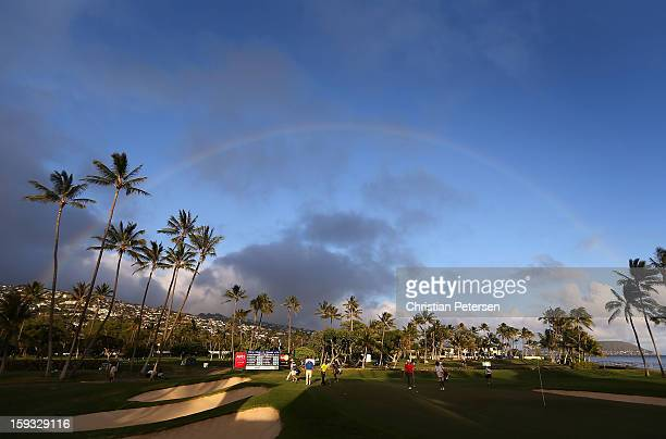 Justin Hicks Josh Persons and Shawn Stefani approach the 17th green under a rainbow during the second round of the Sony Open in Hawaii at Waialae...