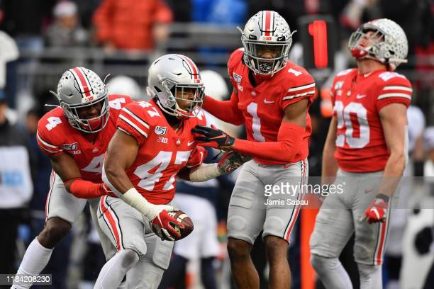 Justin Hilliard of the Ohio State Buckeyes celebrates with teammates /bbd4 and Jeff Okudah after intercepting a Penn State Nittany Lions pass in the...
