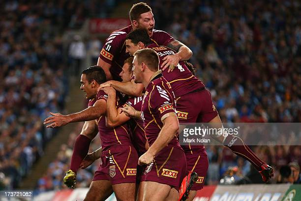 Justin Hodges of the Maroons celebrates with team mates after scoring a try during game three of the ARL State of Origin series between the New South...