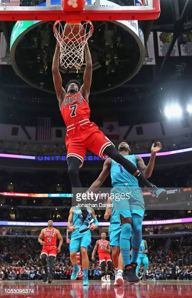 Justin Holiday of the Chicago Bulls dunks over Michael KiddGilchrist of the Charlotte Hornets at the United Center on October 24 2018 in Chicago...