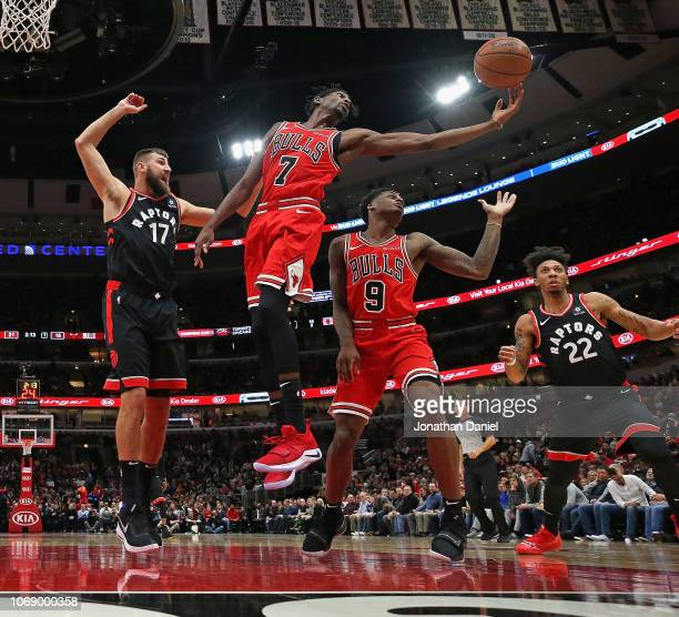 Justin Holiday of the Chicago Bulls rebounds over teammate Antonio Blakeney and Jonas Valanciunas and Malachi Richardson of the Toronto Raptors at...