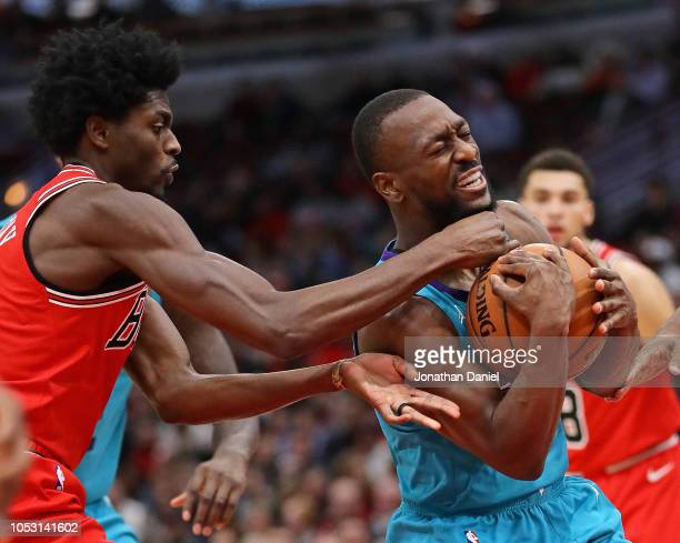 Justin Holiday of the Chicago Bulls tries to grab the ball away from Kemba Walker of the Charlotte Hornets at the United Center on October 24 2018 in...