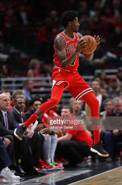 Justin Holiday of the Chicago Bulls tries to keep the ball from going out of bounds against the Utah Jazz at the United Center on December 13 2017 in...
