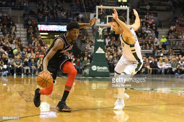 Justin Holiday of the Chicago Bulls works against Matthew Dellavedova of the Milwaukee Bucks during a game at the Bradley Center on December 26 2017...