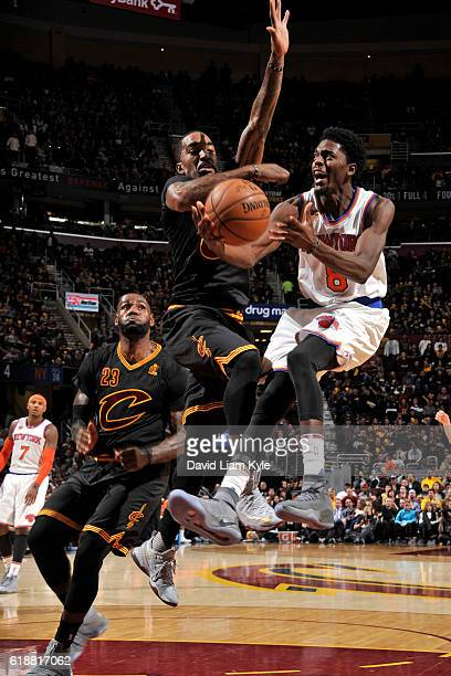 Justin Holiday of the New York Knicks drives to the basket while guarded by JR Smith of the Cleveland Cavaliers on October 25 2016 at Quicken Loans...
