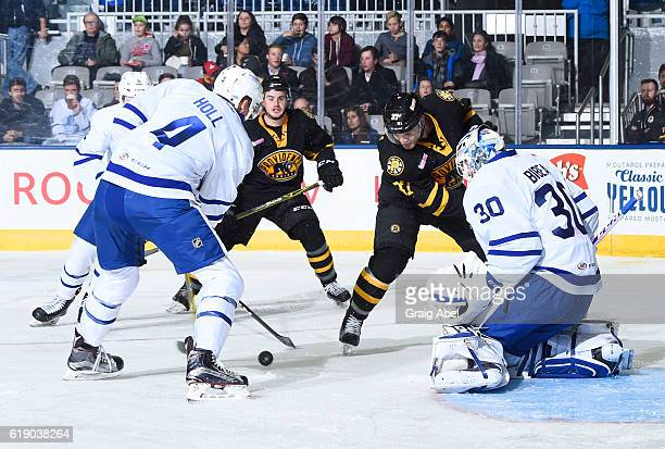 Justin Holl controls the puck in front of goalie Antoine Bibeau of the Toronto Marlies as Jordan Szwarz and Wayne Simpson of the Providence Bruins...