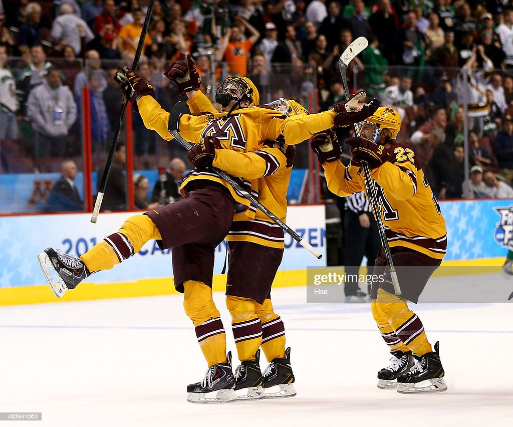 Justin Holl #12 of the Minnesota Golden Gophers celebrates his game winning goal with teammates Sam Warning #11 and Travis Boyd #22 with .6 of a second left in the third period against the North Dakota Fighting Sioux during the 2014 NCAA Division I Men's Hockey Championship Semifinal at Wells Fargo Center on April 10, 2014 in Philadelphia, Pennsylvania.The Gophers defeated the Fighting Sioux 2-1.