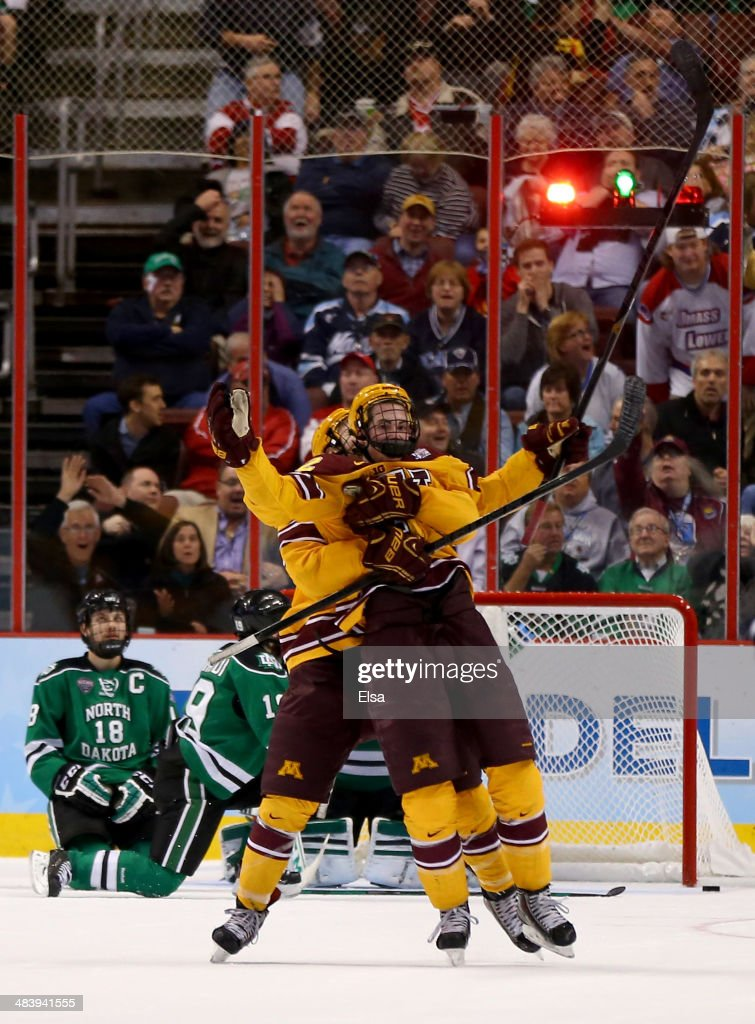 Justin Holl #12 of the Minnesota Golden Gophers celebrates his game winning goal with teammate Seth Ambroz #17 as Dillon Simpson #18 of the North Dakota Fighting Sioux looks on during the 2014 NCAA Division I Men's Hockey Championship Semifinal at Wells Fargo Center on April 10, 2014 in Philadelphia, Pennsylvania.The Gophers defeated the Fighting Sioux 2-1.