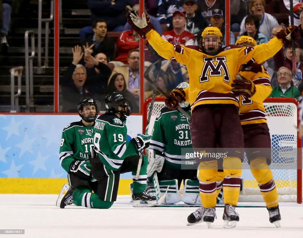 Justin Holl #12 of the Minnesota Golden Gophers celebrates his game winning goal with teammate Seth Ambroz #17 as Dillon Simpson #18 and Rocco Grimaldi #19 of the North Dakota Fighting Sioux looks on during the 2014 NCAA Division I Men's Hockey Championship Semifinal at Wells Fargo Center on April 10, 2014 in Philadelphia, Pennsylvania.The Gophers defeated the Fighting Sioux 2-1.