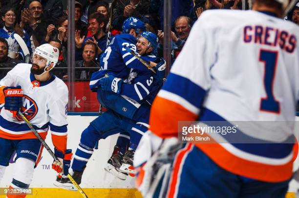 Justin Holl of the Toronto Maple Leafs celebrates with teammate Travis Dermott after scoring his first NHL goal on Thomas Greiss of the New York...