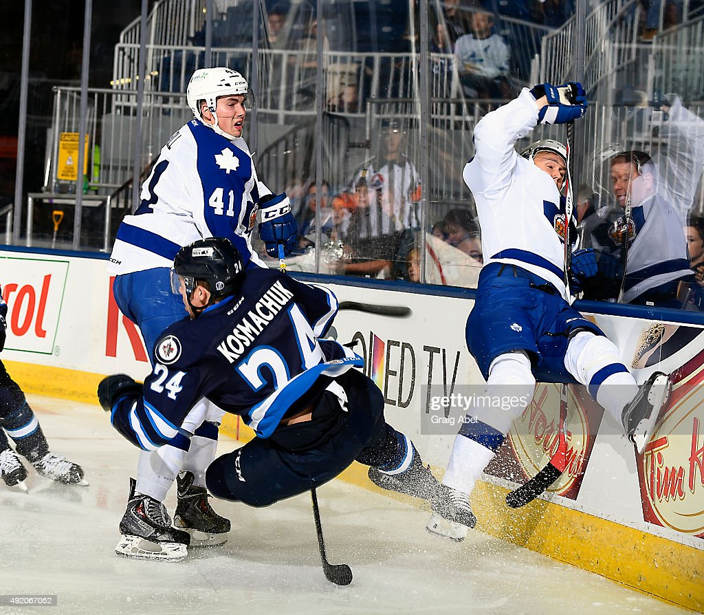 Justin Holl #41 of the Toronto Marlies makes a hit on Scott Kosmachuk #24 of the Manitoba Moose during Opening Night AHL game action on October 9, 2015 at the Ricoh Coliseum in Toronto, Ontario, Canada.