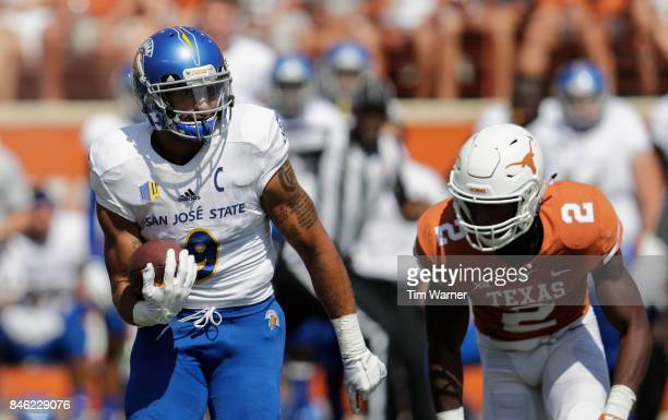 Justin Holmes of the San Jose State Spartans runs the ball pursued by Kris Boyd of the Texas Longhorns in the second quarter at Darrell K RoyalTexas...