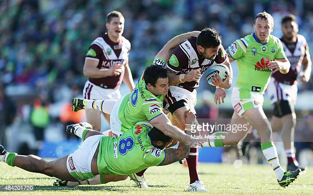 Justin Horo of the Sea Eagles is tackled by David Shillington and Frank-Paul Nuuausala of the Raiders during the round 23 NRL match between the...