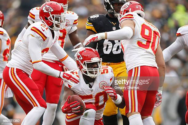 Justin Houston celebrates his fumble recovery with Sean Smith and Josh Mauga of the Kansas City Chiefs during the second quarter against the...