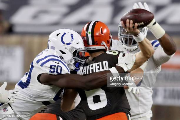 Justin Houston of the Indianapolis Colts hits Baker Mayfield of the Cleveland Browns as he throws a pass in the fourth quarter at FirstEnergy Stadium...