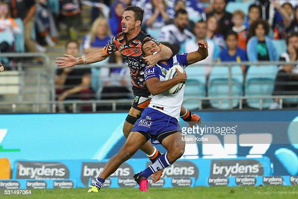Justin Hunt of the Tigers tackles Moses Mbye of the Bulldogs high during the round 10 NRL match between the Wests Tigers and the Canterbury Bulldogs...