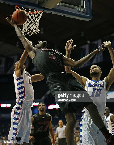 Justin Jackson of the Cincinnati Bearcats leans back to put up a shot against Cleveland Melvin and Derrell Robertson Jr #10 of the DePaul Blue Demons...