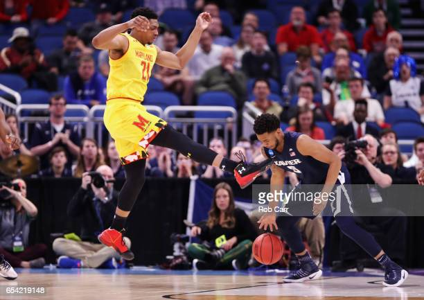 Justin Jackson of the Maryland Terrapins and Trevon Bluiett of the Xavier Musketeers battle for the ball in the first half during the first round of...