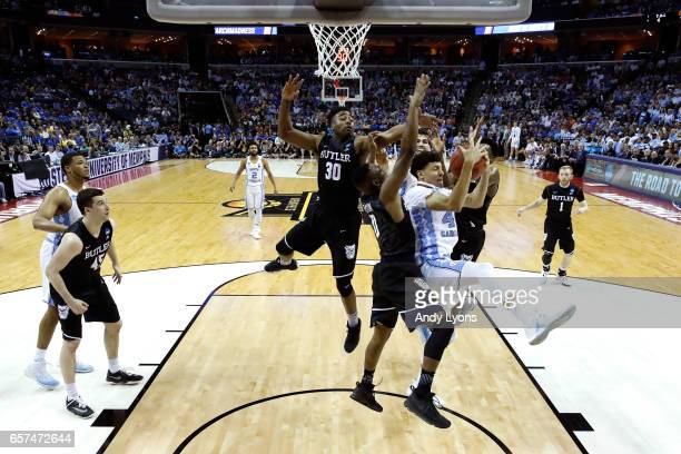 Justin Jackson of the North Carolina Tar Heels gets a rebound in the first half against Avery Woodson and Kamar Baldwin of the Butler Bulldogs during...