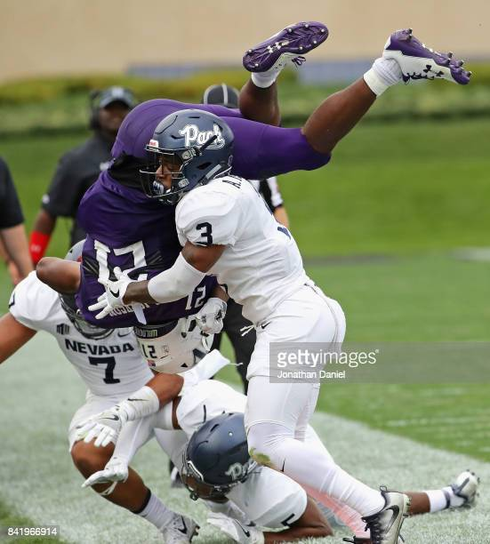 Justin Jackson of the Northwestern Wildcats flips in the air after being hit by Dameon Baber and Ahki Muhammad of the Nevada Wolf Pack at Ryan Field...