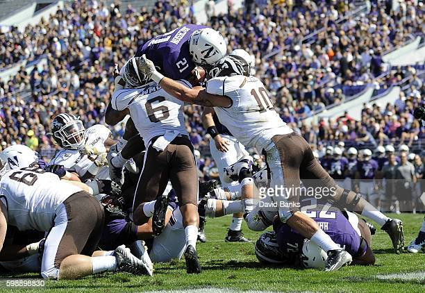 Justin Jackson of the Northwestern Wildcats is tackled by Asantay Brown of the Western Michigan Broncos and Robert Spillane during the first half on...